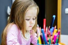 Милая маленькая девочка studing к говорить и писать письма дома стоковые изображения