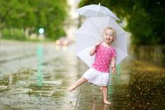 Милая маленькая девушка малыша имея потеху под дождем стоковая фотография