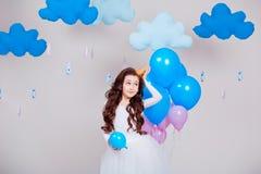 Милая маленькая девушка принцессы стоя среди воздушных шаров в комнате над белой предпосылкой смотреть камеру Детство Стоковая Фотография RF