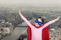 Милая маленькая девушка супергероя в красном плаще стоковое изображение rf