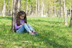Милая маленькая длинн-с волосами девушка сидя на траве в парке с мобильным телефоном в ее руках и посылая сообщение на черни теле Стоковая Фотография RF