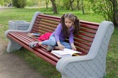 Милая маленькая кавказская книга чтения девушки сидя на стенде Стоковая Фотография RF