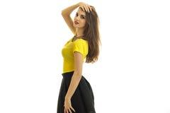 Милая милая девушка в желтых блузке и юбке стоит косой к камере и держит ее руку около волос Стоковая Фотография RF