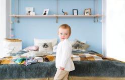 Милая милая младенческая девушка в белом свитере стоя на кровати с подушками в спальне Стоковое Изображение