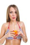 Милая молодая женщина в бикини выпивая апельсиновый сок Стоковые Фотографии RF