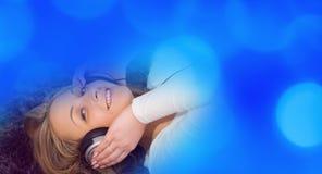 Милая молодая женщина в наушниках слушая к музыке и голубым светам Стоковая Фотография RF