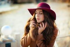 Милая молодая женщина в шляпе и пальто с ей глаза закрыла конец вверх стоковые фото