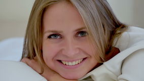 Милая молодая женщина лежа на ее кровати усмехаясь на камере акции видеоматериалы