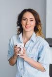 Милая молодая женщина держа кружку и усмехаться Стоковые Изображения