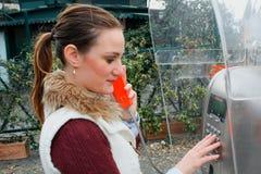 Милая молодая женщина имея звонок на общественном телефоне Стоковое Фото