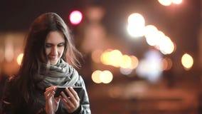 Милая молодая женщина используя ее smartphone на ноче Дама в улице в холоде самомоднейшая технология сток-видео