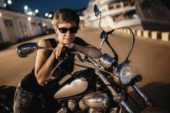 Милая молодая женщина и мотоцикл брюнет на улице Одессы стоковая фотография