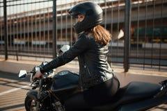 Милая молодая женщина и мотоцикл брюнет стоковая фотография rf