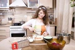 Милая молодая женщина на кухне подготавливая обедающий Стоковое Фото