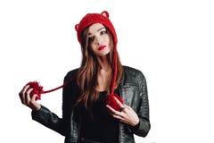 Милая молодая женщина нося руку связала красную шляпу на белой предпосылке изолировано Красивая девушка внутри с щитком уха Стоковое Изображение RF