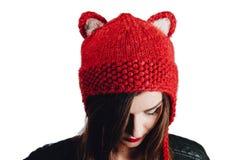 Милая молодая женщина нося руку связала красную шляпу на белой предпосылке изолировано Красивая девушка внутри с щитком уха Стоковые Изображения RF