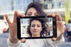 Милая молодая женщина принимает selfie с умным телефоном Стоковая Фотография RF