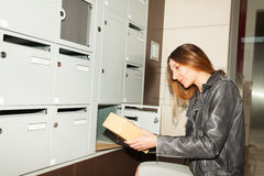 Милая молодая женщина принимая пакет от почтового ящика Стоковое фото RF
