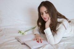 Милая молодая женщина, при красивые длинные волосы лежа на кровати Стоковая Фотография RF