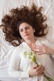 Милая молодая женщина, при красивые длинные волосы лежа на кровати стоковые фото