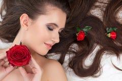 Милая молодая женщина расслабляющая с цветками стоковая фотография rf