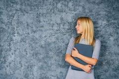 Милая молодая женщина стоя с портативным компьютером Стоковое Изображение