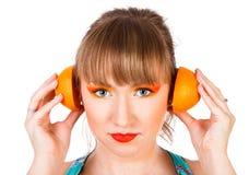 Милая молодая женщина с половины оранжевого плодоовощ около ее ушей Стоковые Фото