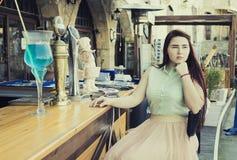 милая молодая женщина с темными длинными волосами и голубым eyesl сидит на a Стоковая Фотография RF