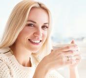 Милая молодая женщина с чашкой кофе в солнечном ресторане стоковое фото