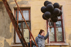 Милая молодая женщина с черными воздушными шарами Стоковые Изображения RF