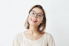 Милая молодая милая девушка в стеклах усмехаясь показывающ язык смотря камеру над белой предпосылкой Стоковое Фото