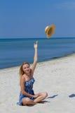 Милая молодая сексуальная девушка с шляпой, в голубом платье сидя на пляже, предпосылка моря Концепция свободы и потехи Стоковое фото RF