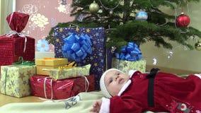 Милая ложь ребёнка около коробок рождественской елки и подарка присутствующих видеоматериал