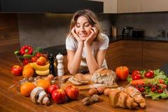 Милая домохозяйка смотря серию еды на кухонном столе стоковая фотография rf