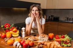 Милая домохозяйка смотря серию еды на кухонном столе стоковое изображение
