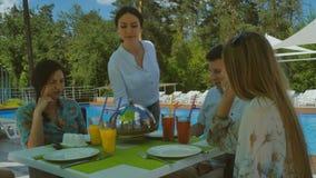Милая официантка приносит вкусное блюдо к компании 4 друзей около бассейна сток-видео