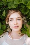 Милая очаровательная молодая женщина лежа на листьях и одуванчиках зеленого цвета Стоковая Фотография