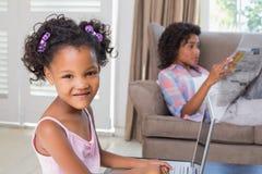 Милая дочь используя компьтер-книжку на столе с матерью на кресле Стоковая Фотография RF
