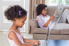 Милая дочь используя компьтер-книжку на столе с матерью на кресле Стоковое Изображение RF