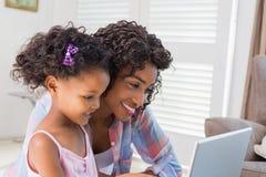 Милая дочь используя компьтер-книжку на столе с матерью Стоковые Изображения RF