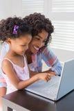 Милая дочь используя компьтер-книжку на столе с матерью Стоковое Фото