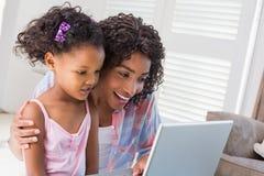 Милая дочь используя компьтер-книжку на столе с матерью Стоковая Фотография