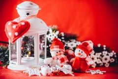 Милая пара маленьких снеговиков стоит около белого fairy фонарика с сердцем игрушки на ей и украшенной ветви ели Стоковое Фото
