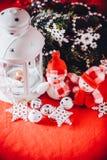 Милая пара маленьких снеговиков стоит около белого fairy фонарика с сердцем игрушки на ей и украшенной ветви ели Стоковое Изображение