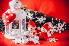 Милая пара маленьких снеговиков стоит около белого fairy фонарика с сердцем игрушки на ей и украшенной ветви ели Стоковая Фотография