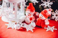 Милая пара маленьких снеговиков стоит около белого fairy фонарика с сердцем игрушки на ей и украшенной ветви ели Стоковые Изображения RF