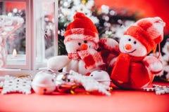 Милая пара маленьких снеговиков стоит около белого fairy фонарика с сердцем игрушки на ей и украшенной ветви ели Стоковые Фотографии RF