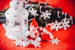 Милая пара маленьких снеговиков стоит около белого fairy фонарика с сердцем игрушки на ей и украшенной ветви ели Стоковые Изображения