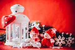 Милая пара маленьких снеговиков стоит около белого fairy фонарика с сердцем игрушки на ей и украшенной ветви ели Стоковые Фото