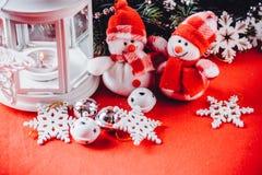 Милая пара маленьких снеговиков стоит около белого fairy фонарика Стоковые Фотографии RF